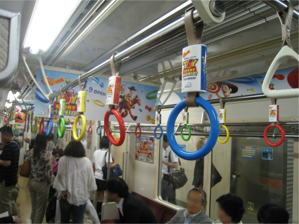通常は三角形の吊り輪を期間限定で、赤・黄・青・緑のカラフルな輪っかにしている(東京メトロ銀座線)。