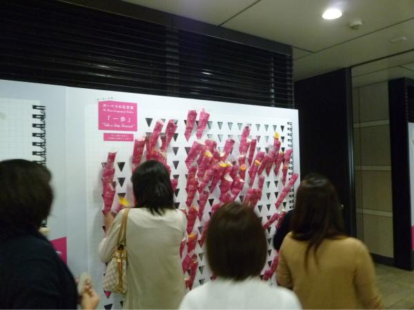 広告面に差し込まれたガーベラの花と、それを取っていく女性たち。