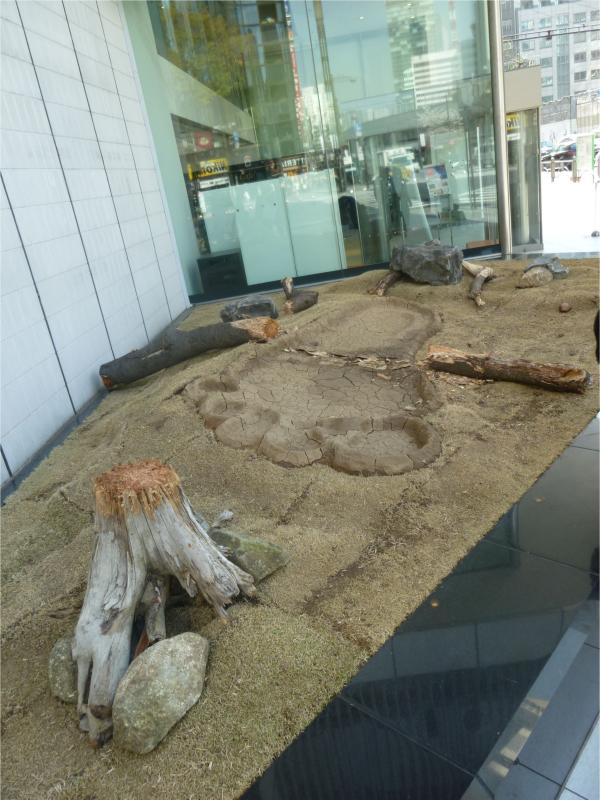 巨人の実物大の足あとと踏みつけられた木が表現されている(ソニービル イベントスペース)。