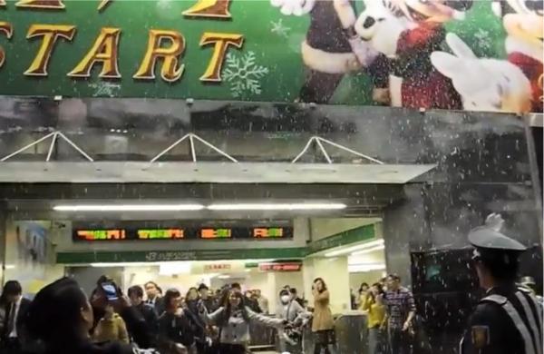 改札を出て雪が降っていることに気づき、驚く人たち