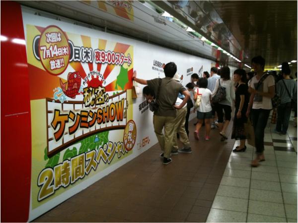 広告の前に、多くの人が集まっている様子。