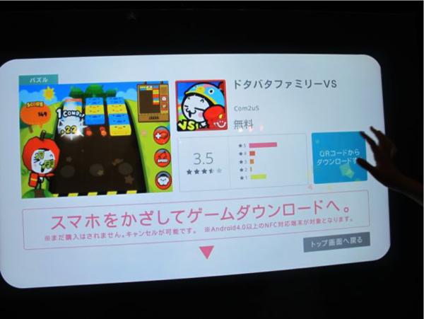 タッチパネル式の画面上でゲームを選び、Android搭載スマホでタッチするとゲームがDLされる。