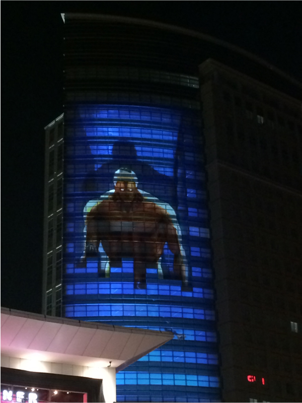 ビル壁面に映し出された 60m級の巨人