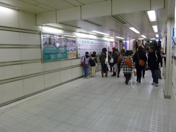 ポスターの前に集まる人たちと、その集まっている様子を見る通行者