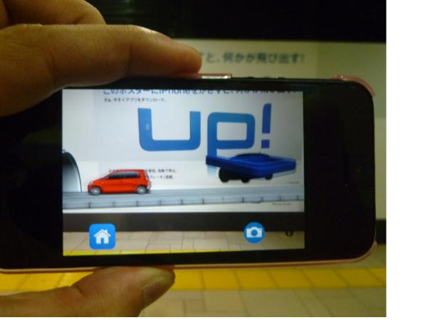 スマホ越しに現れるAR動画。突然落ちてきた「UP!」のロゴに対して、車が自動でストップするという内容となっている。