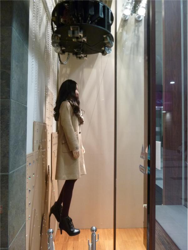 ブランドの服を着た男女のマリオネットが吊るされている。