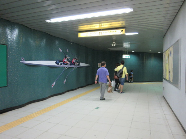 """駅に元々備え付けられた""""波打つ壁面""""をうまく活用したボートの展示(赤羽橋駅)"""