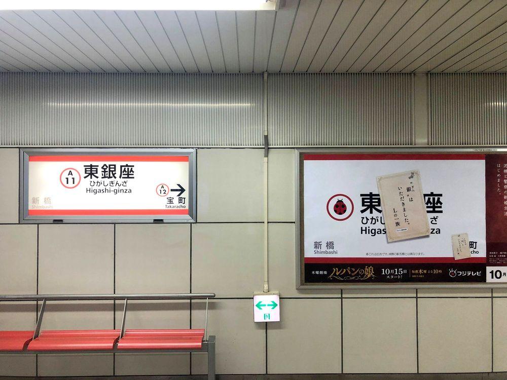 駅名表示と並ぶポスター