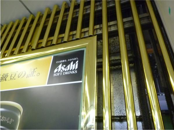 金色のシートが貼られたポスター枠と柵